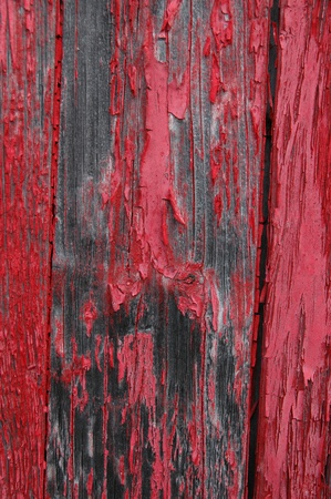 gritty: Black stains on shed siding board with flaking red paint.