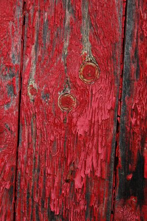dilapidated wall: Black stains on shed siding board with flaking red paint.