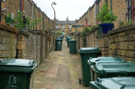 Garbage day. Back alley with garbage bins in a town in England. Stock Photo - 10986662