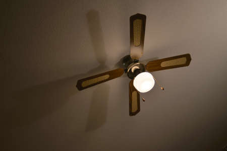 Mediterranean brown wood and material ceiling fan casts a long shadow on a plaster ceiling.