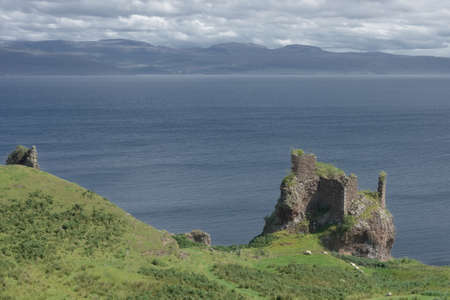 Old ruined coastal castle, brochel castle, on the shores of the inner sound and isle of Raasay in scotland. Sunny day with a cloudy sky.