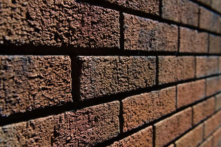 4 - Abstract selective focus side view of harshly lit red brick wall. Lines converge into the blurred distance. Lit by bright sunlight.