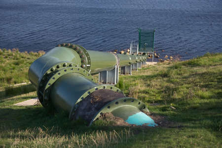 Full frame image of large green metal pipe in an outdoor hydro dam setting. Modern and bolted together, with control equipment at the reservoir end