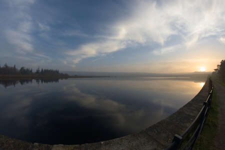 Middle reservoir at redmires reservoirs near sheffield, flat calm at sunset. Fish eye perspective as the water reflects the sunset sky of wispy clouds