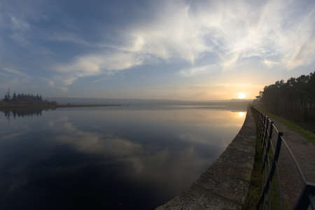 Sunset and clouds reflected in the water of redmires reservoir near sheffield. Level horizon, but fish eye distortion elsewhere. Expansive cloudscape Stock fotó