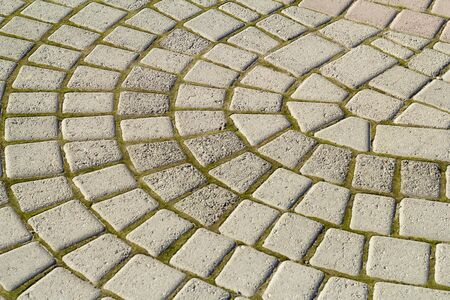 Symmetrical pattern of sidewalk tile with green moss .Grey pavement stone texture