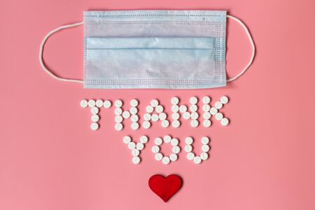 Internationals nurses day, week concept, Text Thank you by tablets and red heart on pink background.