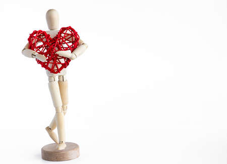 Wooden mannequin holding rattan red heart. White background.