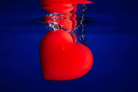 falling water: A red heart falling into blue water with bubble floating to surface