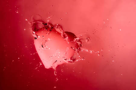 A pink heart splashing onto the surface of water with pink background. photo