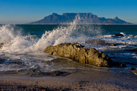 seascapes: Sunrize over Table Mountain with crocodile looking rock in foreground and ocean spray