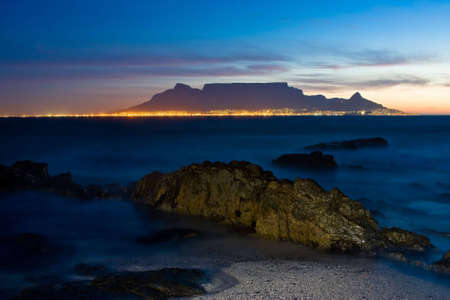 Sunset over Table Mountain with crocodile looking rock in foreground and city skyline photo