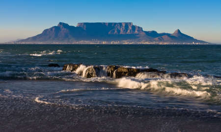 capetown: Early morning waves overlooking table mountain from blouberg starnd