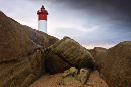 Umhlanga Lighthouse on the rocky coast of South Africa photo