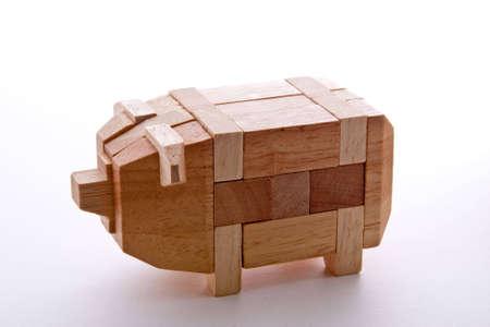 disassemble: Wooden Pig Interlocking puzzle isolated on white