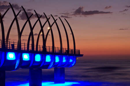 Sunrise over Umlanga Pier with blue lights reflecting in the ocean photo