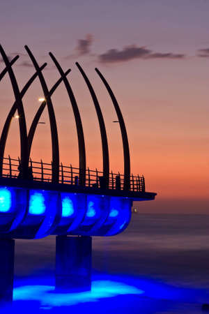 Sunrise over Umlanga Pier with blue lights reflecting in the ocean