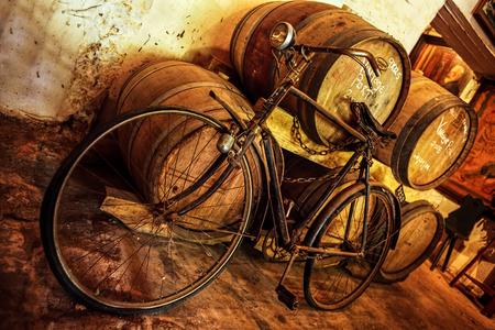 Rusty alten Fahrrad im Keller gelehnt Weinfässer Standard-Bild - 23175428