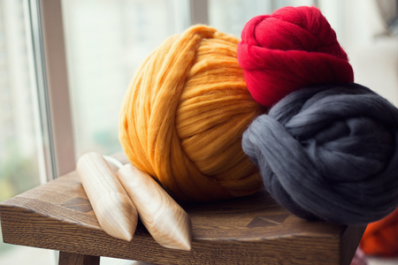 Wooden knitting needles and merino wool balls, lying on wooden stool, composition near the window