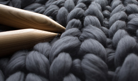 wooden knitting needles on background of grey merino wool blanket