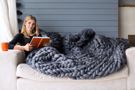 cosy: Cozy composition, closeup of woman reading book on merino wool plaid having a rest, warm and comfortable atmosphere.