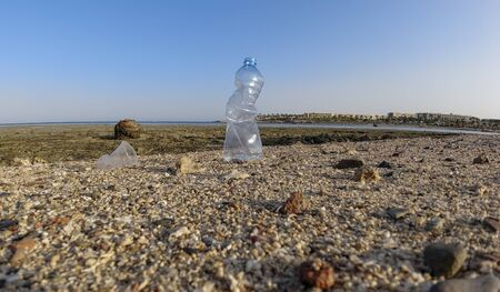 Plastic bottle on the shore against the backdrop of a coral reef at low tide. Environmental hazard