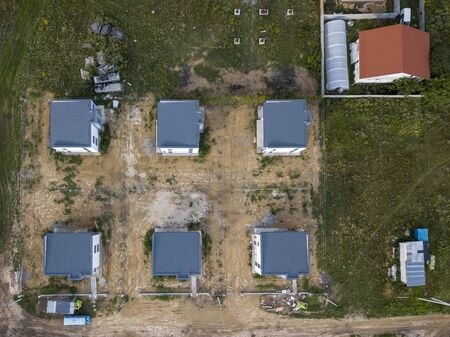 Construction of cottage houses in a vacant lot with an access dirt road Aerial view