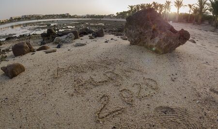 The inscription on the sand of Marsa Alam 2020 at low tide against the backdrop of hotels and reef with sun flare