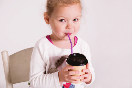 Little girl holding a paper coffee cup to take away and smile