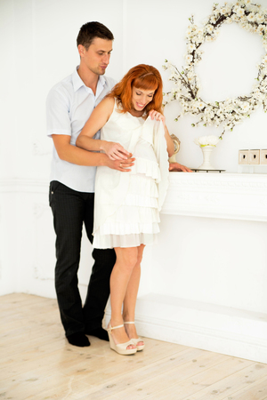 A pregnant wife and husband stand in white decoration