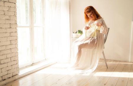 pregnant woman sits near a window