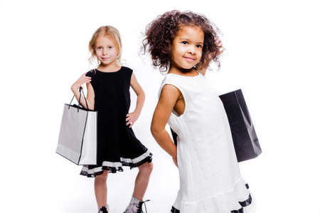 Little fashionable girls girlfriends of two different nationalities posing on a white background with shopping bags.