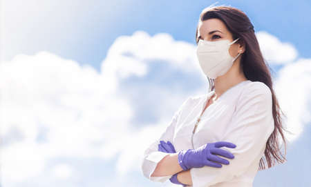 A beautiful brunette girl in a medical suit, a protective mask on her face and gloves posing against a background of blue sky and clouds. The girl stands with crossed arms and looks into the distance. Horizontal photo