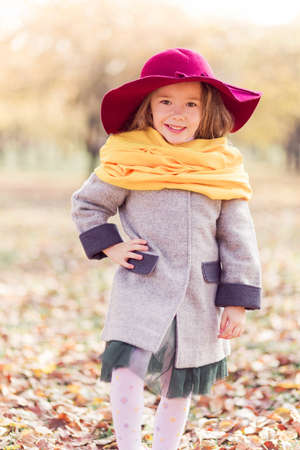 Beautiful little girl in a gray coat, a yellow scarf and a burgundy hat posing for the camera in an autumn park. Vertical photo