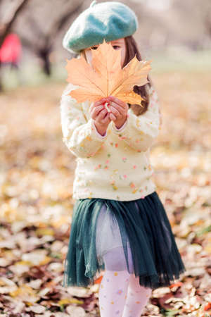 Beautiful little girl in a beret, yellow sweater and green tulle skirt in an autumn park. A girl holding an autumn yellow leaf in her hands. Vertical photo