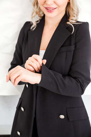 A blonde girl in a black suit stands against a white wall and straightens her sleeve. Vertical photo