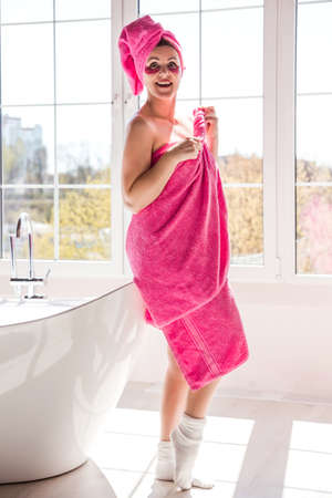 A beautiful and happy woman with a body and hair wrapped in a pink towel and with pink patches under her eyes is posing in a sunny bathroom. Vertical photo
