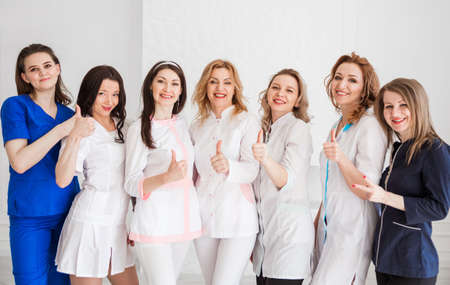 Beautiful young female doctors in white uniforms posing against the background of a white wall, showing the class with their hand and look at the camera and smiles. Horizontal photo