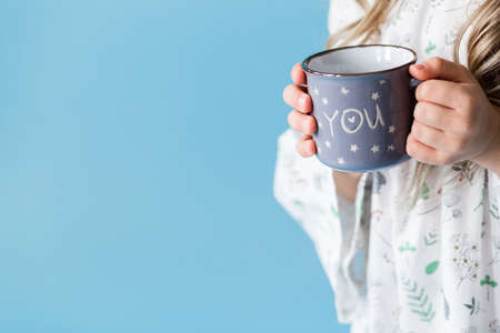 A little girl in a white dress stands against a blue background and holds a cup in her hands. Horizontal photo Stock fotó