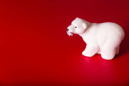 Toy polar bear with fish in mouth on red background. Horizontal photo