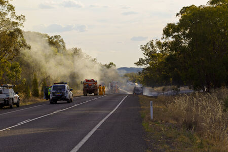 Fire fighters and police attending a car fire on the road near Parkes, NSW, Australia