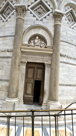 inclination: Entry door to the Leaning Tower of Pisa with a beautiful lunette above the door. The image depicts the actual inclination of the tower.