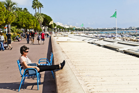 azur: Tourists walking along the Bouleverd de la Croisette in the film festival city of Cannes, Cote d?Azur, France. In the foreground a tourist seating on one of the chairs provided by the city council and enjoying the September sun. Editorial