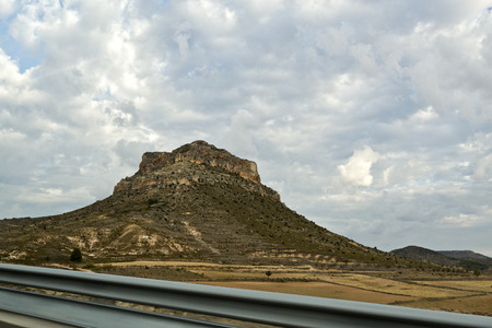 steep cliffs: Mesa in the arid central Spain country seen from the highway. Mesas are elevated areas of land with a flat top and sides that are usually steep cliffs formed by weathering and erosion of horizontally layered rocks. Stock Photo