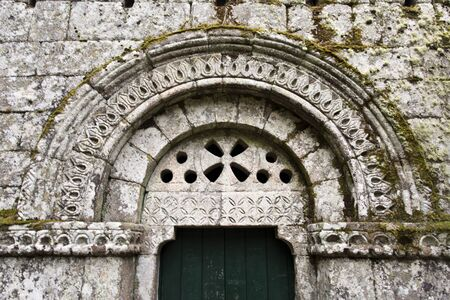 entranceway: Detail of the lintel, pillars and tympanum over the entranceway to the church of the Monastery of Pitoes , Portugal Stock Photo