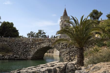 conde: The stone bridge crossing the inlet near the Palace of Conde de Castro Guimaraes, also known as the Tower of Saint Sebastien, in Cascais, Portugal Stock Photo