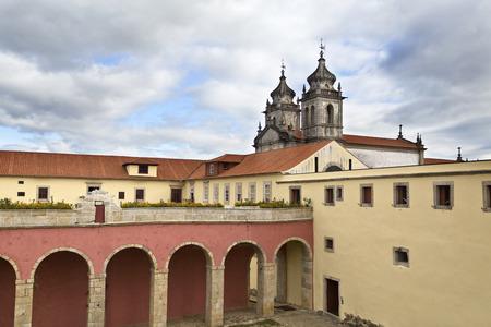 hospedaje: Vista de la vía de paso entre los cuartos coristas y el alojamiento en casa con la iglesia en el fondo del Monasterio de Sao Martinho en Tibaes, Portugal Foto de archivo