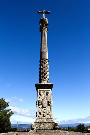 corinthian column: The Stone Cross of Tibaes is a Renaissance monument comprising a Corinthian column and capital with a sphere and a Latin cross on top. Stock Photo