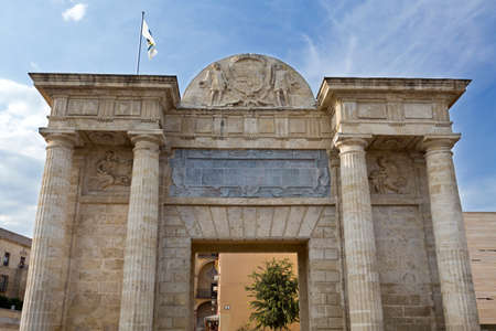 surmounted: Detail of the Puerta del Puente, a Renaissance gate with a central square passage, sided by two couples of Doric columns, surmounted by a Classic-style entablature in Córdoba, Spain