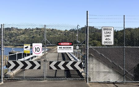 shut: View of a shut gate and multiple warning signs Stock Photo
